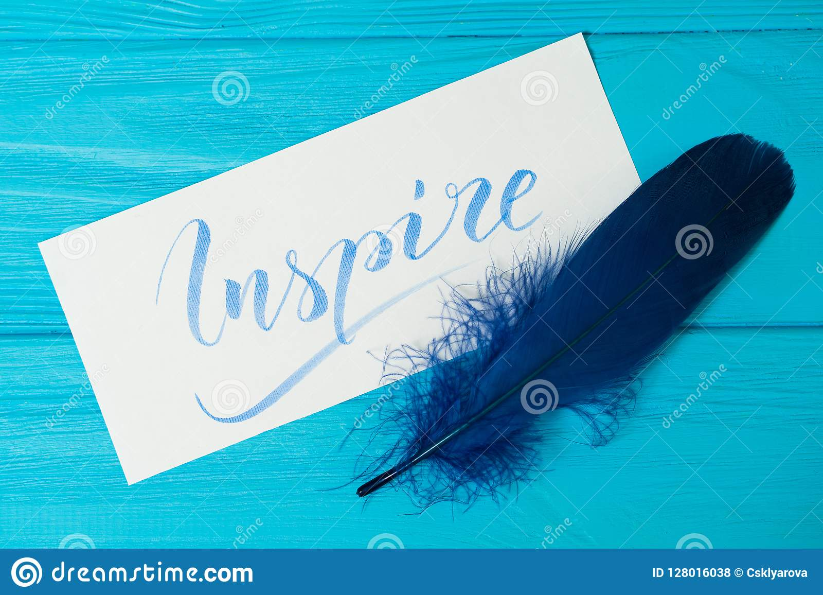 Inspire. Beautiful blue letters on canvas with blue feather. Calligraphy script. Art of writing letters. Background