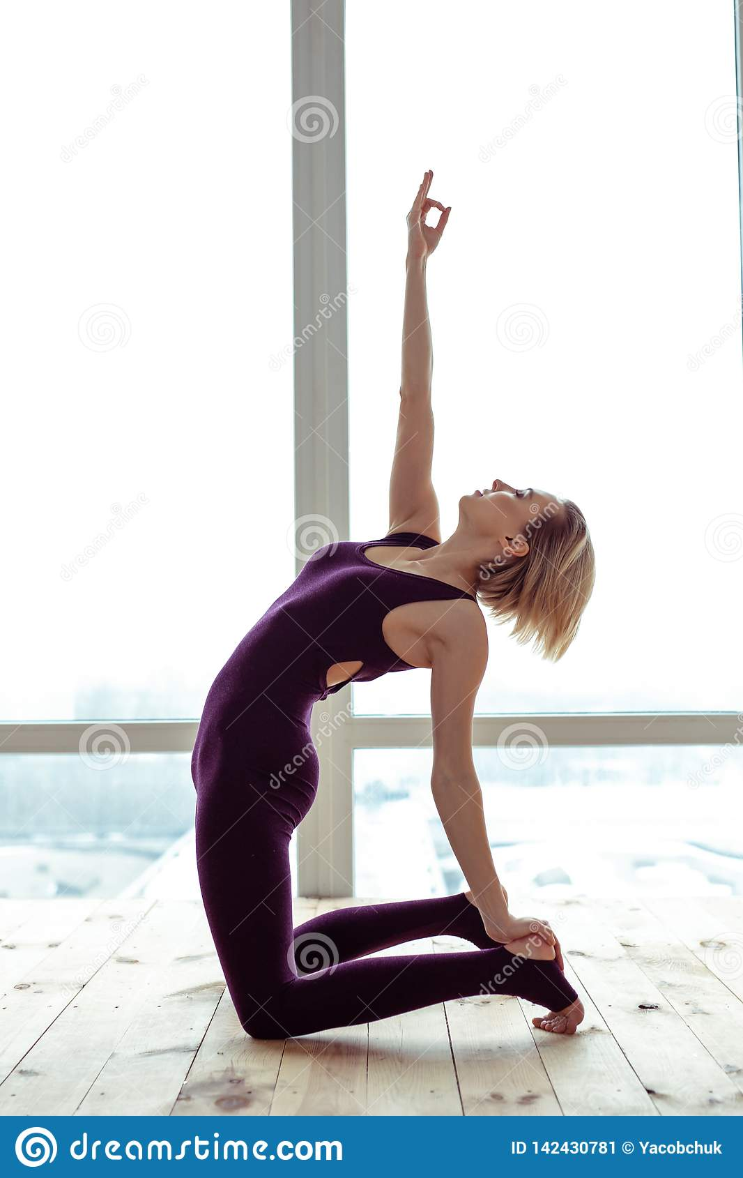 Inspired tranquil lady doing yoga with closed eyes