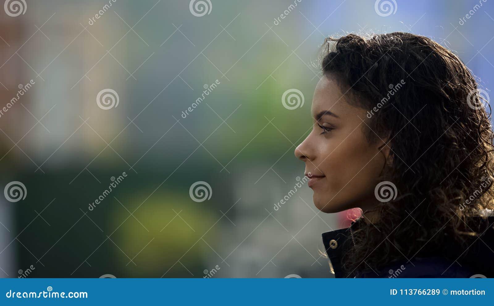 Inspirowany kobieta model ono uśmiecha się, piękny biracial młoda dama portret w profilu