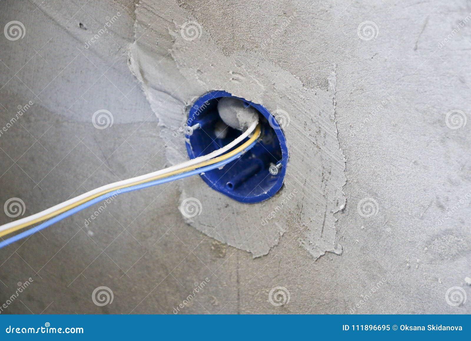 Instalación del enchufe de pared Trabajo sobre la instalación de los mercados eléctricos El electricista prepara los mercados apr