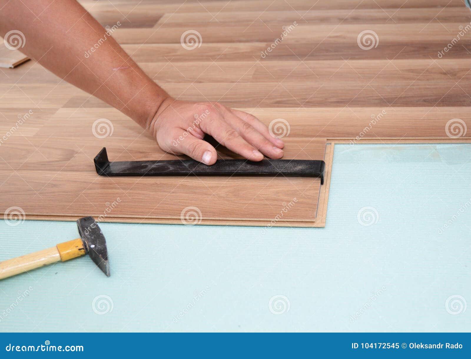 Instalación del suelo laminado Hombre que instala el nuevo suelo de madera laminado Trabajador que instala el suelo laminado de m
