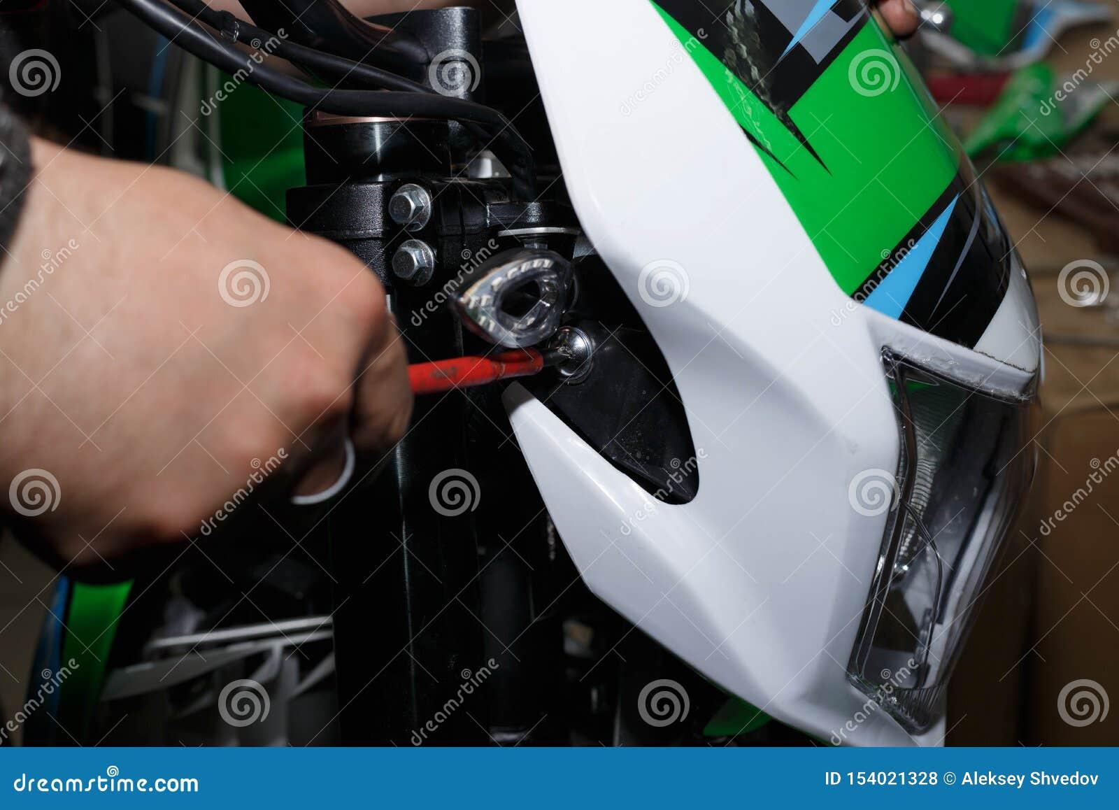 Installation de la lampe avant avec une doublure en plastique sur la moto