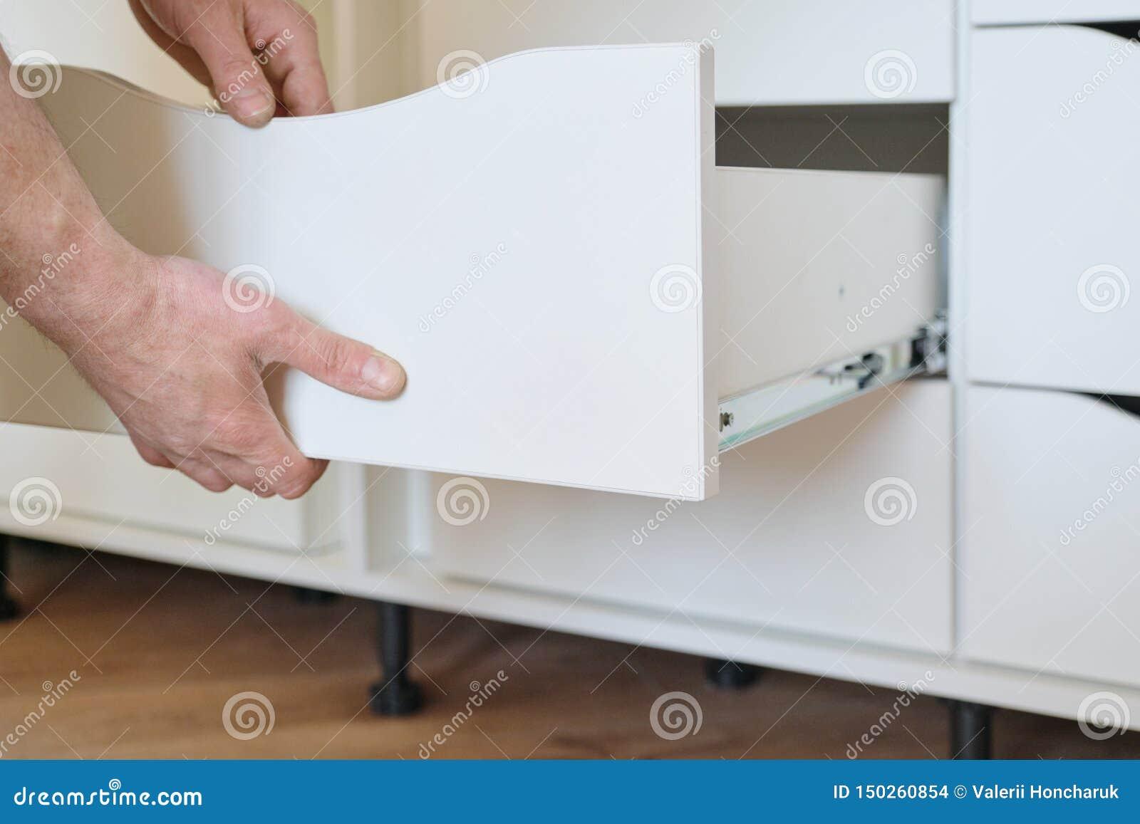 Installation des meubles Le plan rapproché des travailleurs remettent et des petits groupes de meubles