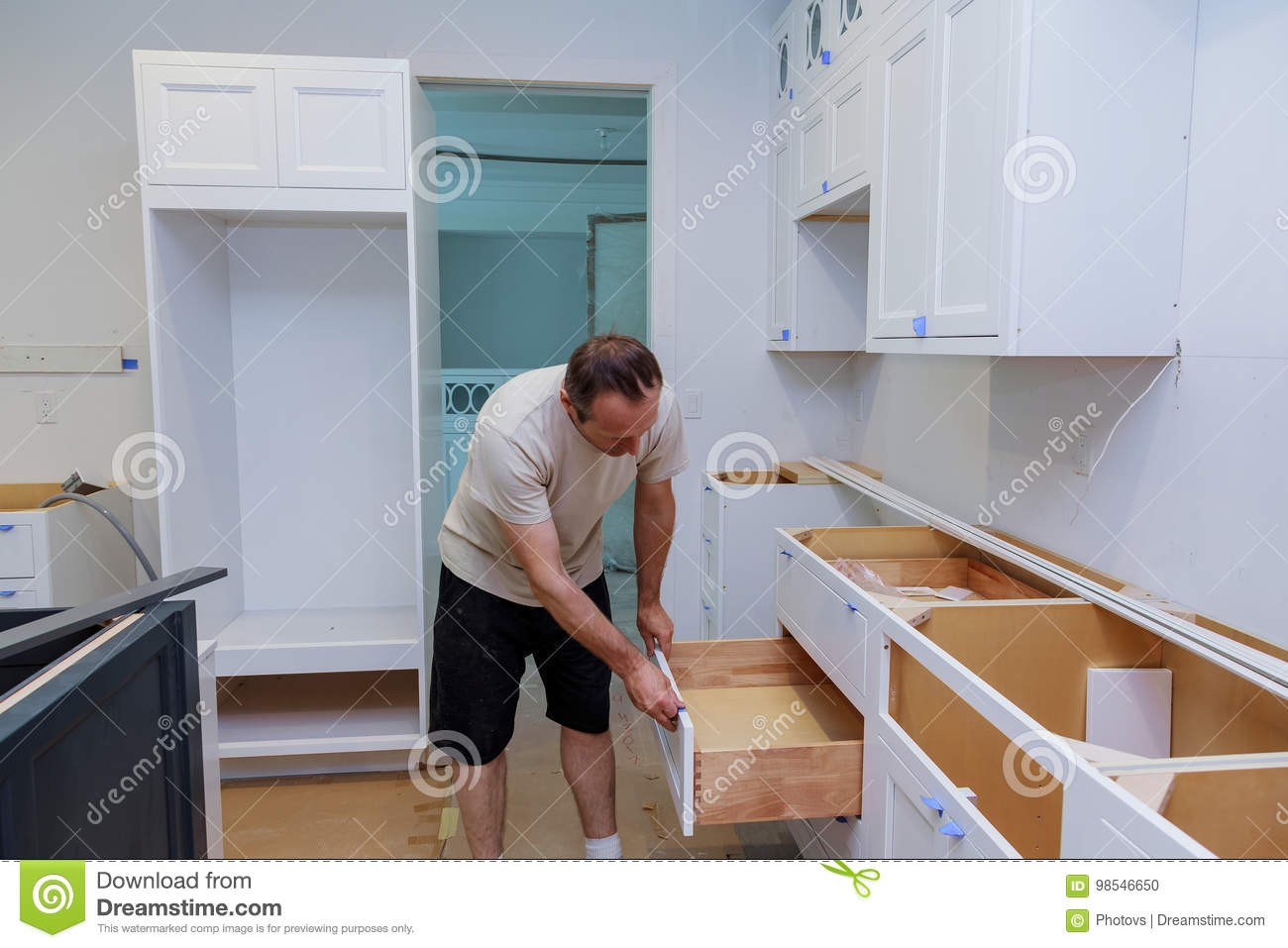 Installation Kitchen. Worker Installs Doors To Kitchen Cabinet ...