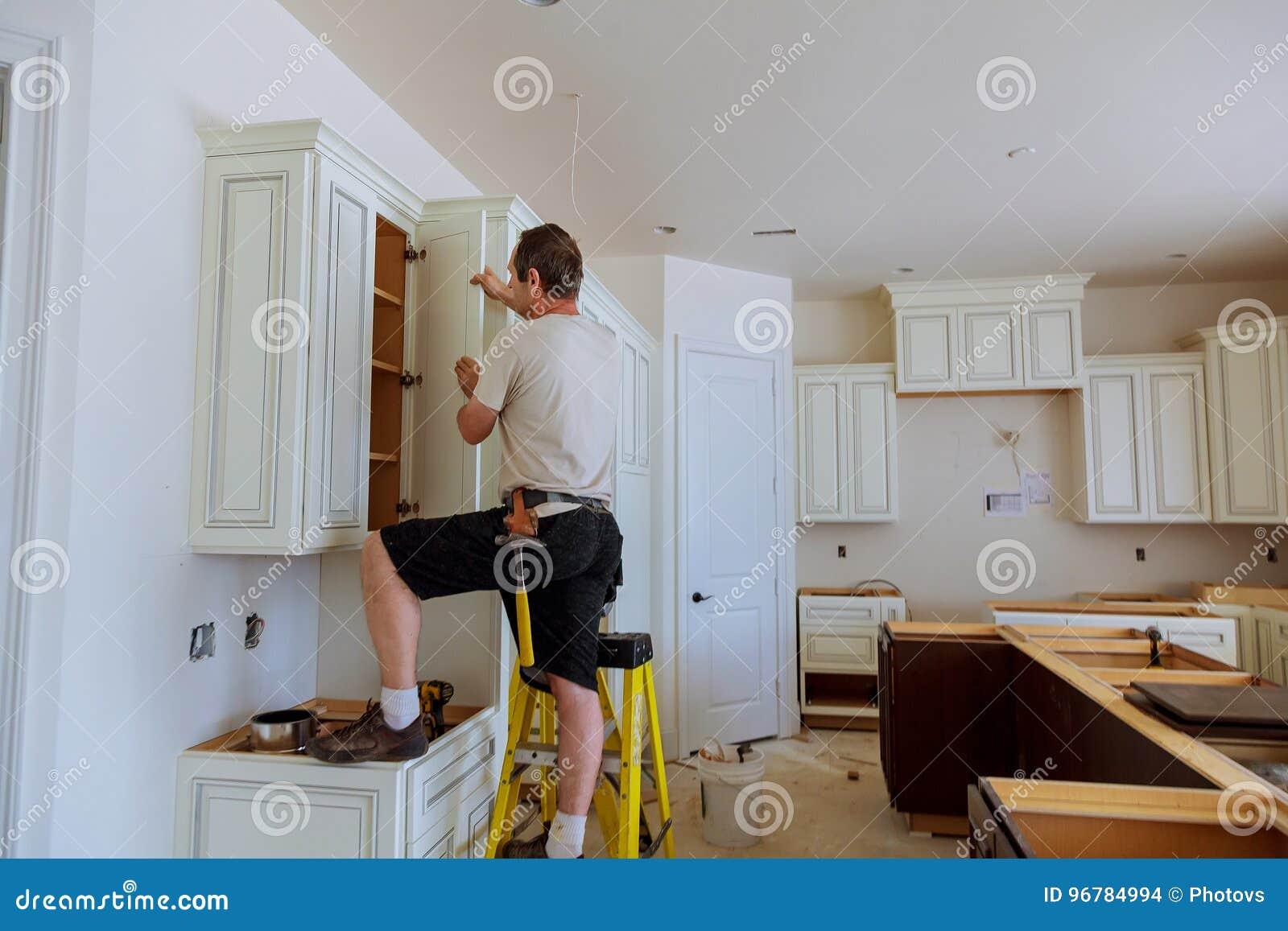Installation Of Kitchen. Worker Installs Doors To Kitchen ...