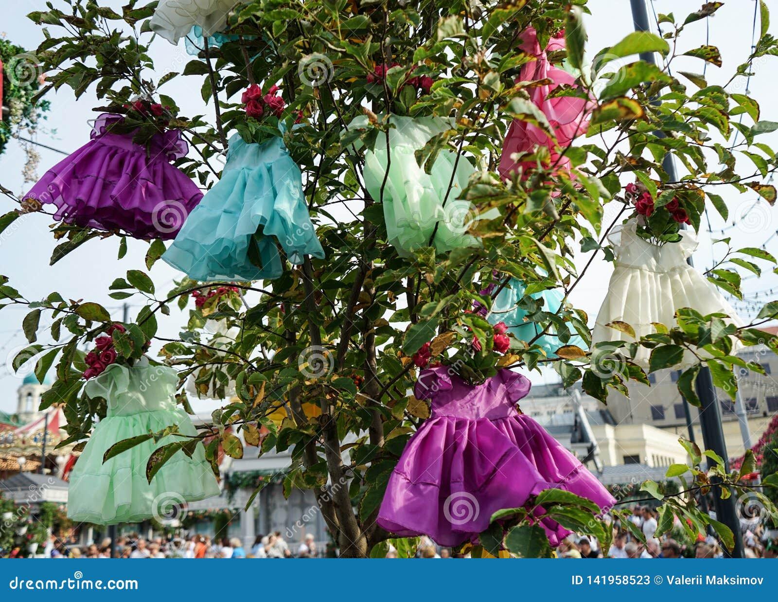 Installation mit den Kleidern der hängenden Kinder auf dem Baum