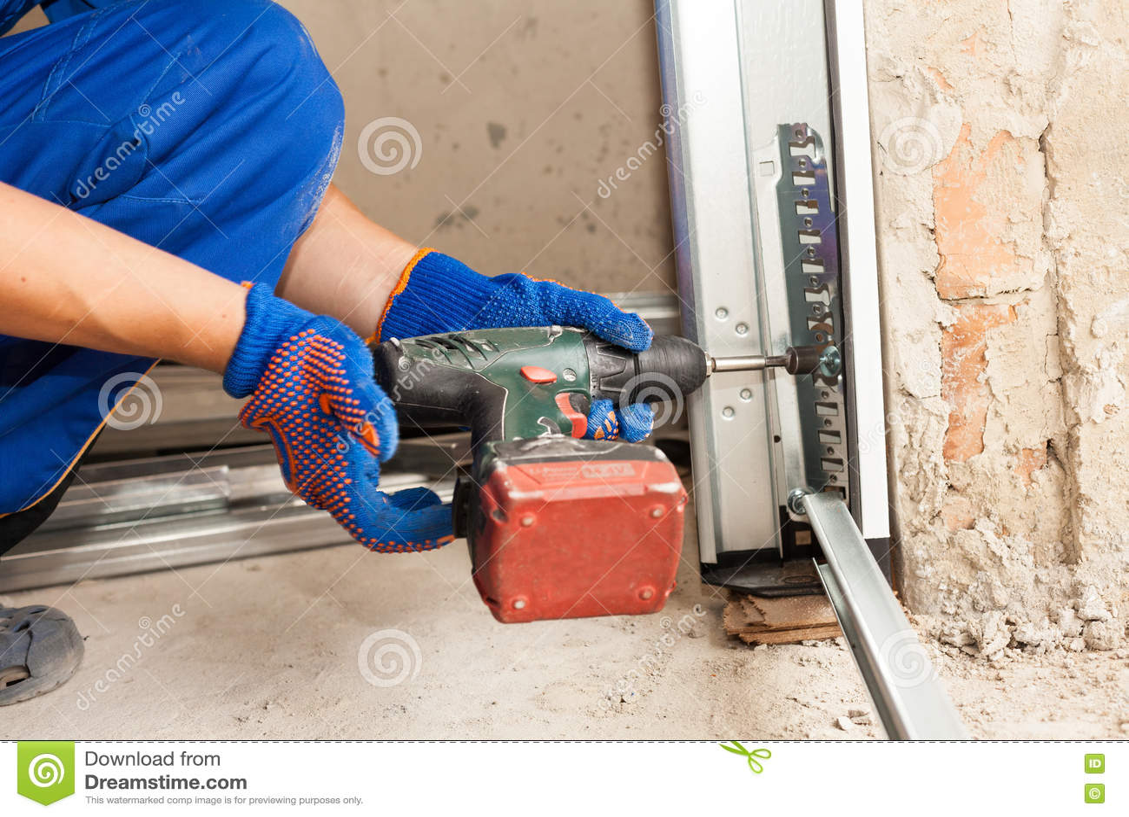 Installazione delle porte del garage Cacciavite automatico di uso del lavoratore per riparare un bullone