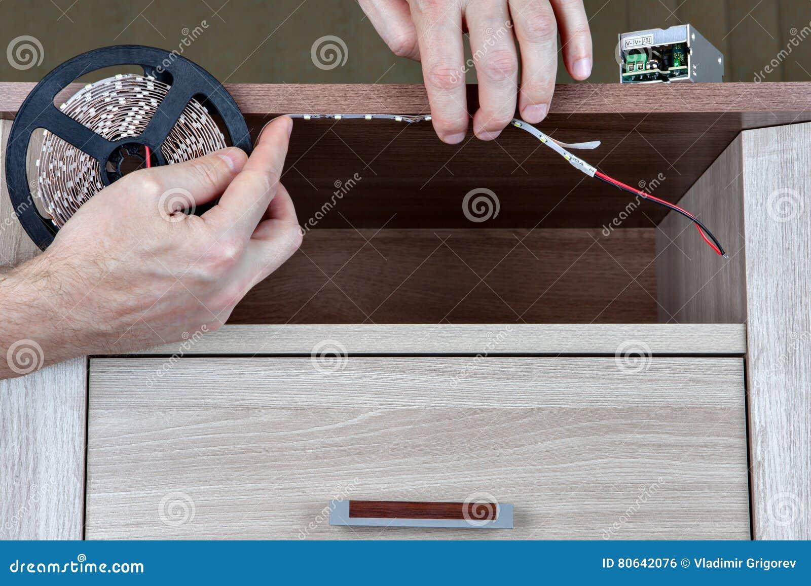 Installing LED Lighting Inside Furniture Cabinet, Hands Man Close Up. Stock Photo