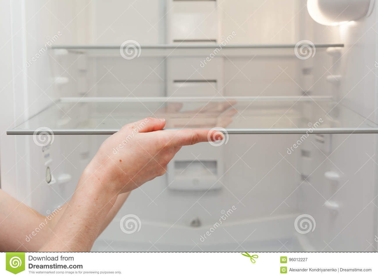 Installing new, clean shelves in an empty washed refrigerator. Young woman cleaning refrigerator