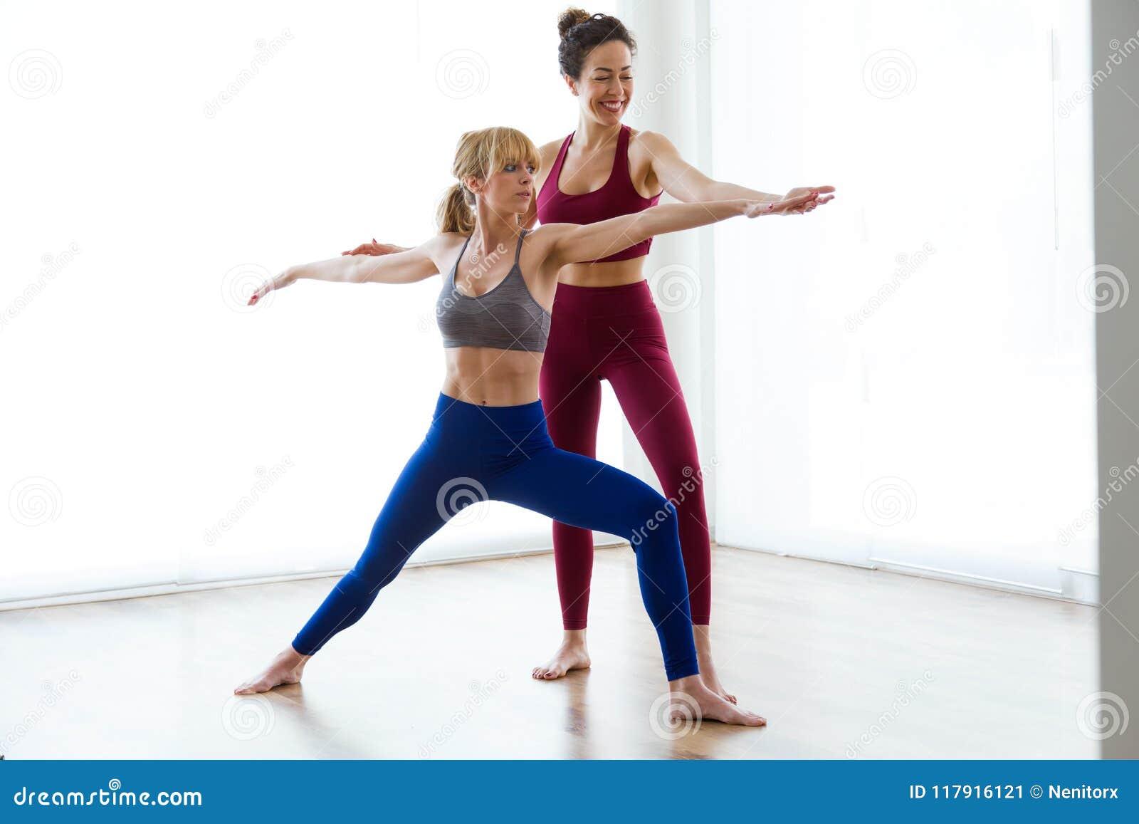 Instructeur assez jeune de yoga aidant son étudiant en session de yoga à la maison Pose de Virabhadrasana II