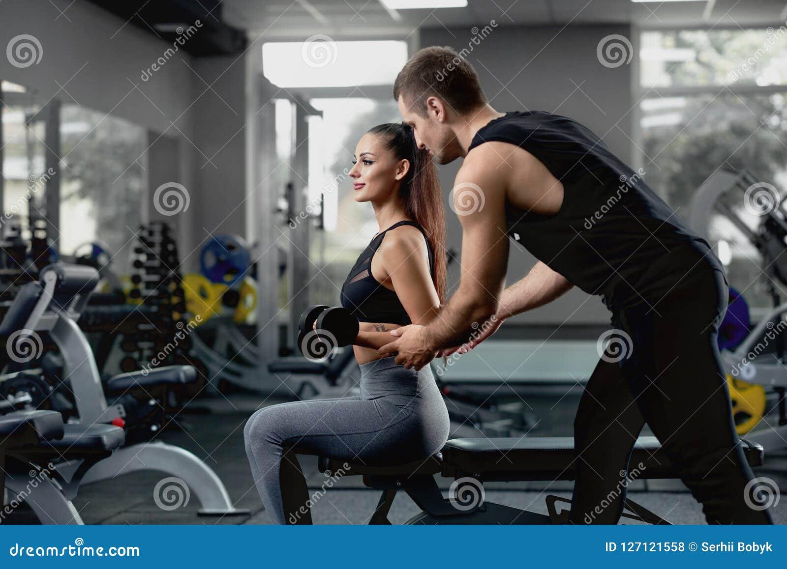 Instructeur personnel bel aidant son client féminin à la formation avec des haltères