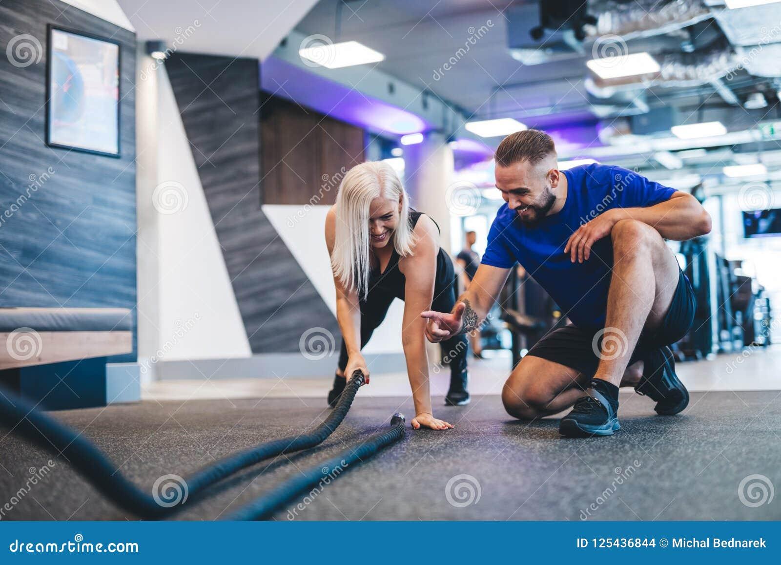 Instructor de gimnasio y una mujer que ejercita en el gimnasio