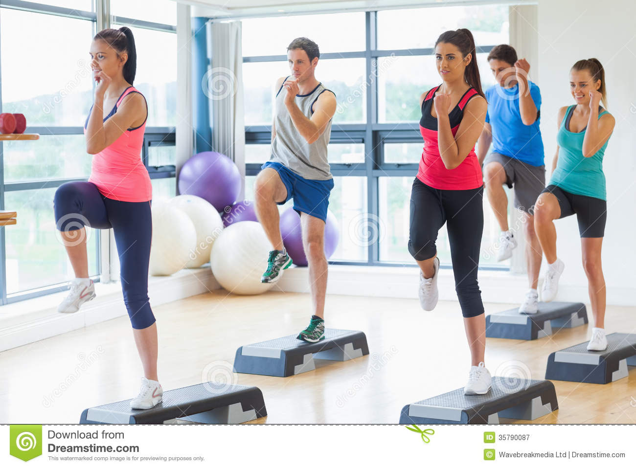 Instructor with fitness class performing step aerobics for Fitness gym