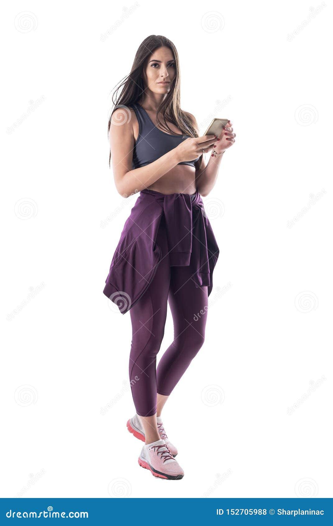 Instructor joven confiado de los aeróbicos en ropa deportiva usando el teléfono móvil que mira la cámara