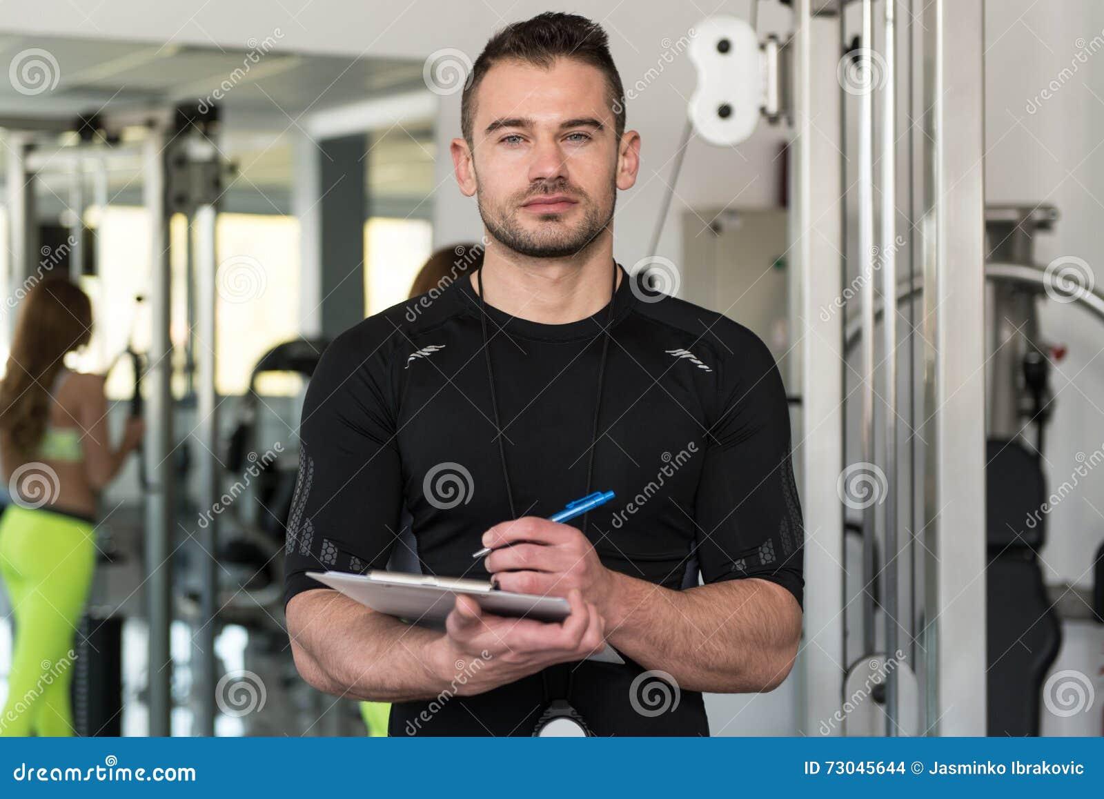 Instructor masculino hermoso With Clipboard In un gimnasio