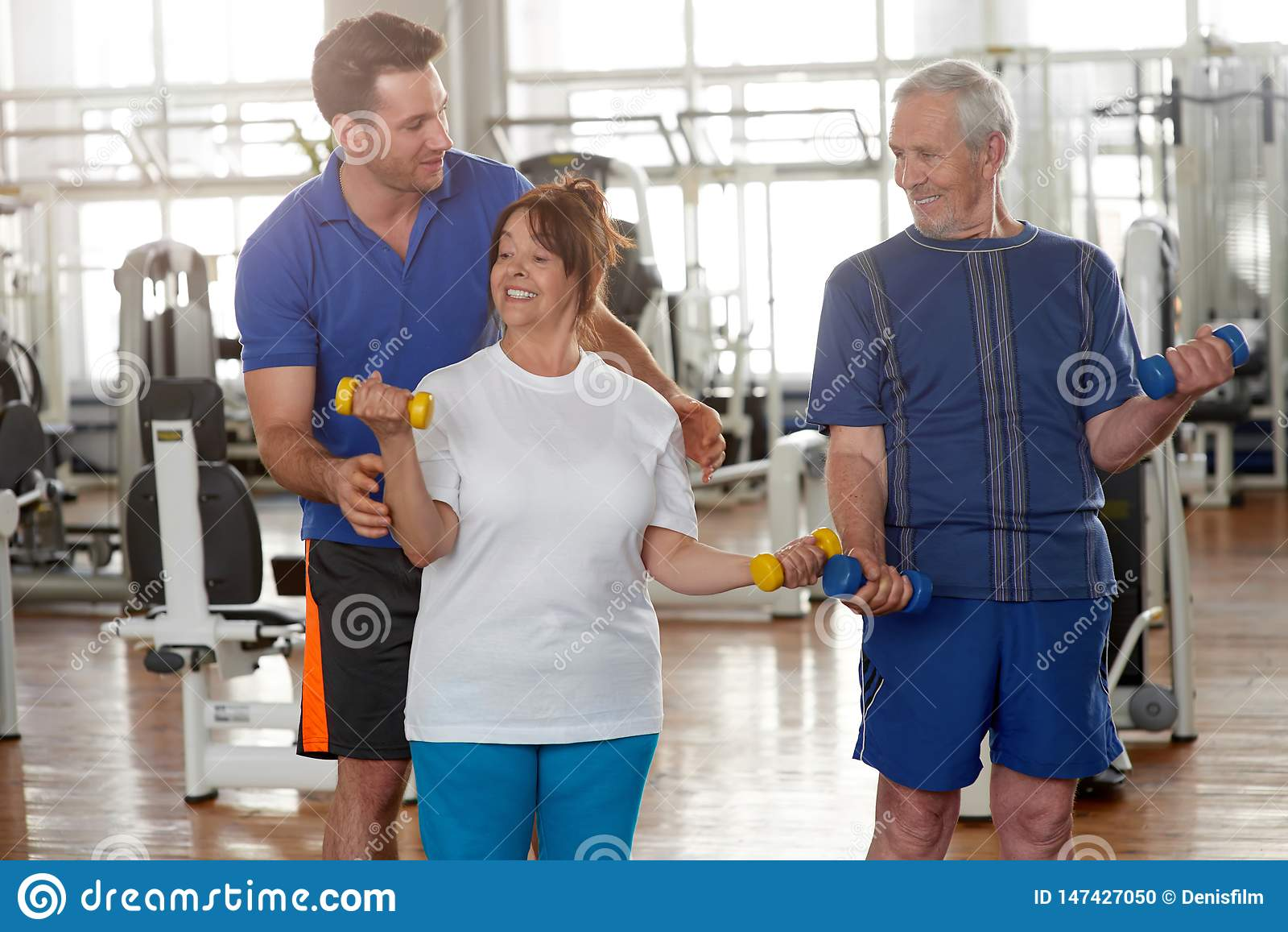 Instructor masculino hermoso que da instrucciones a la mujer mayor en gimnasio