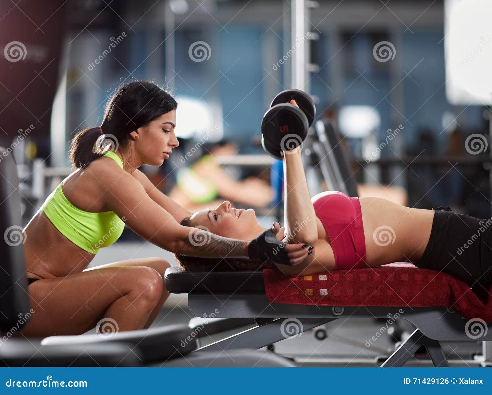 Instructor personal de la mujer en el gimnasio