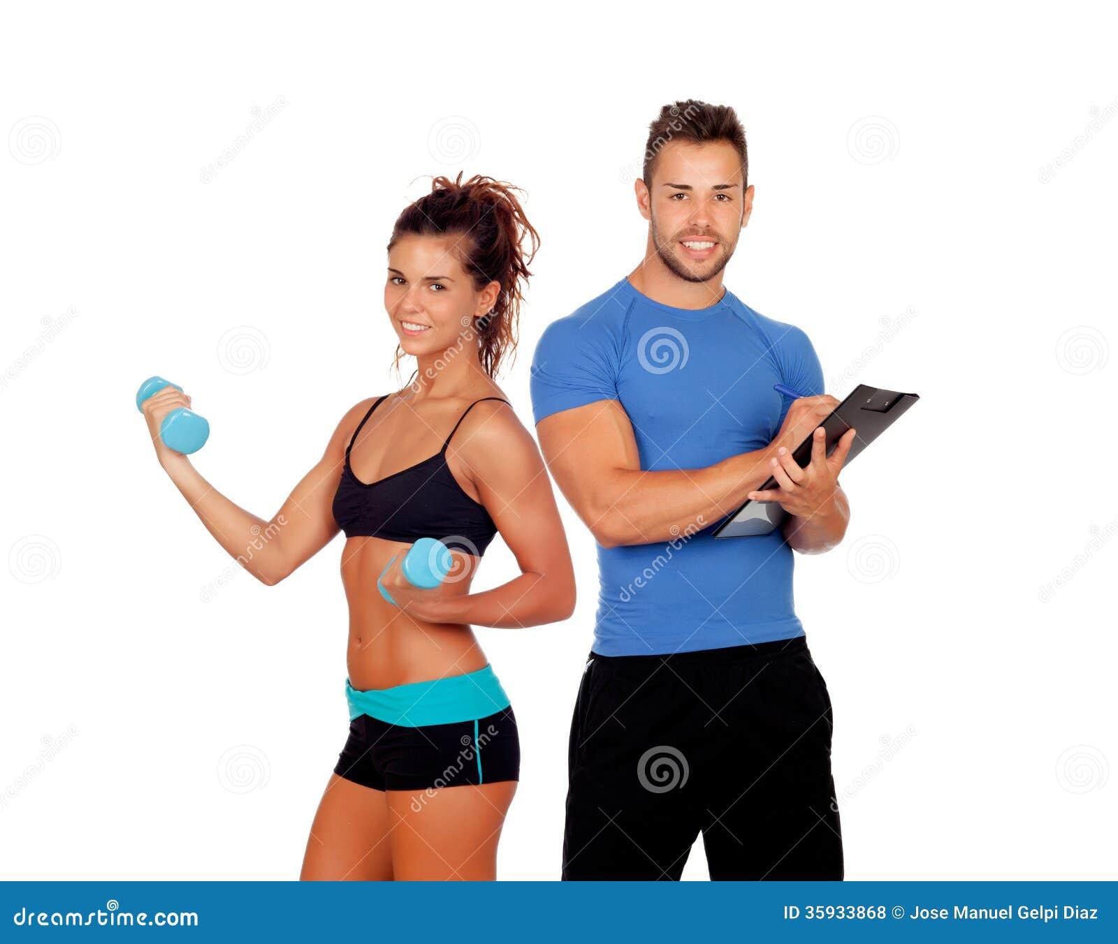 Instructor personal hermoso con la muchacha hermosa con pesas de gimnasia