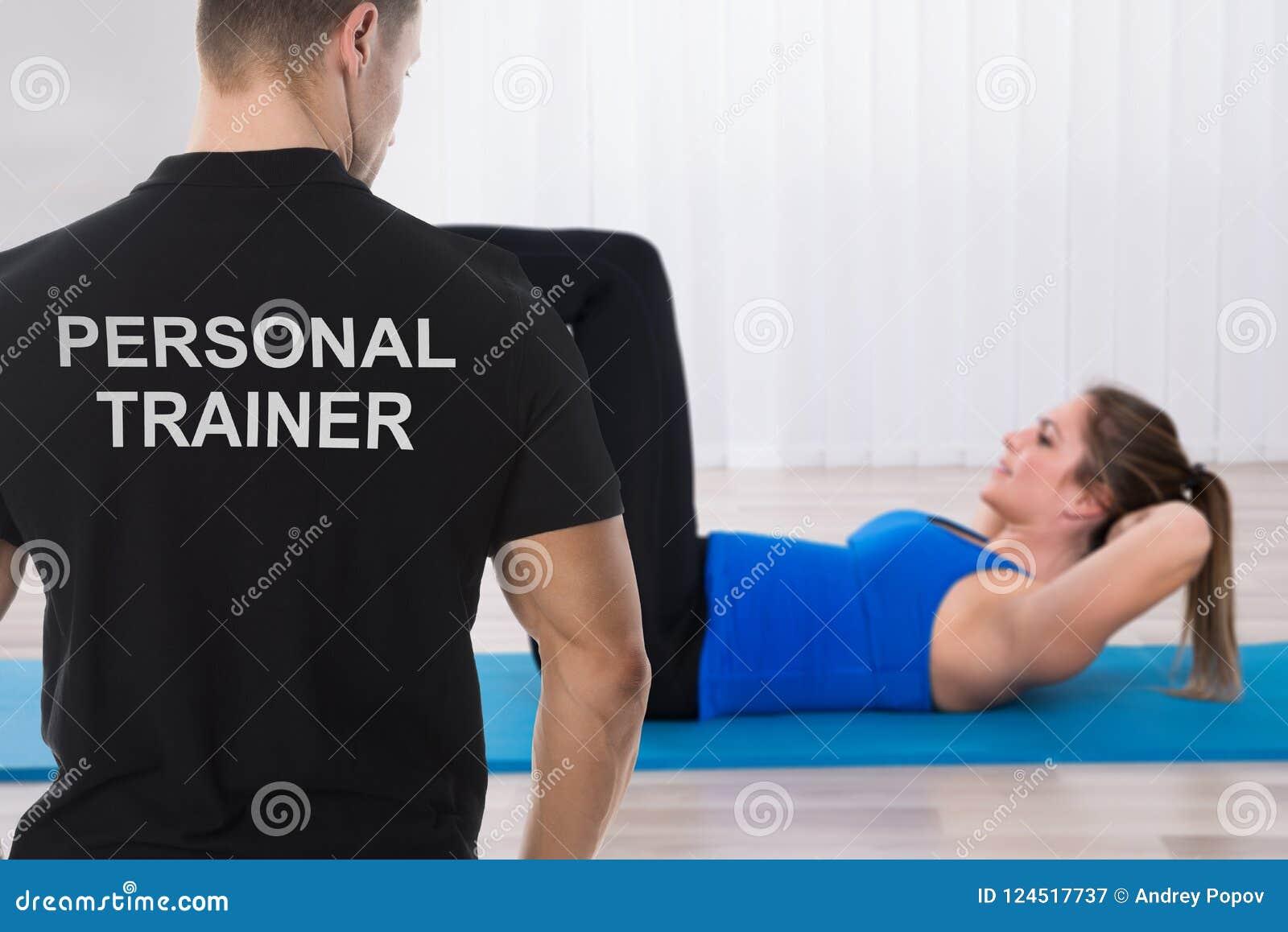 Instructor personal Looking At Woman que hace ejercicio