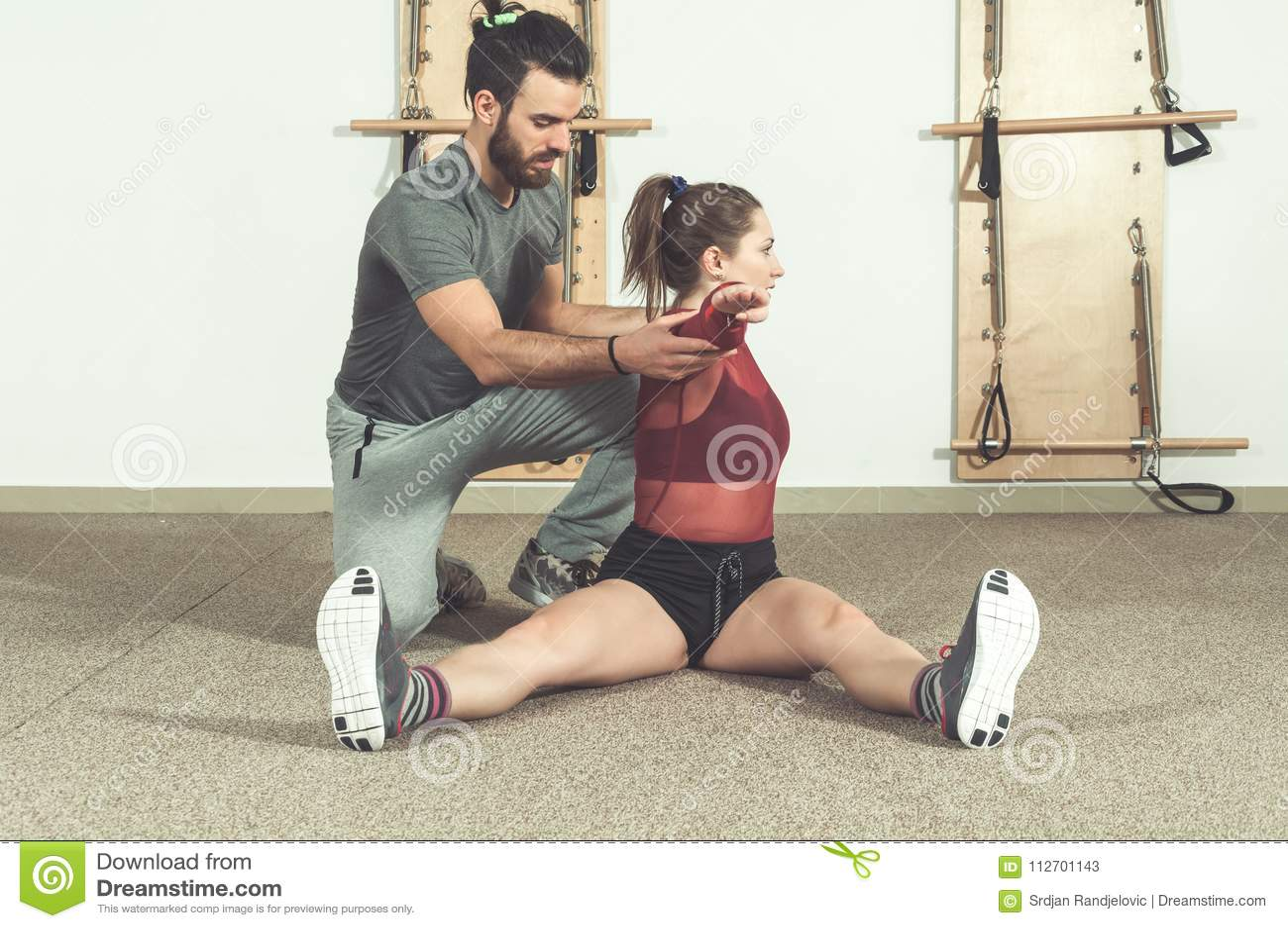 Instructor personal masculino hermoso con una barba que ayuda a la muchacha joven de la aptitud a estirar sus músculos después de