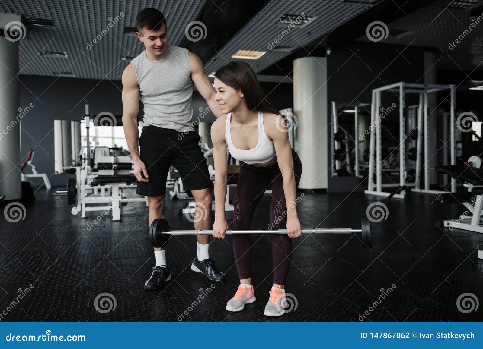 Instructor personal posiciones en cuclillas de ayuda de una mujer joven con los dumbells en un gimnasio