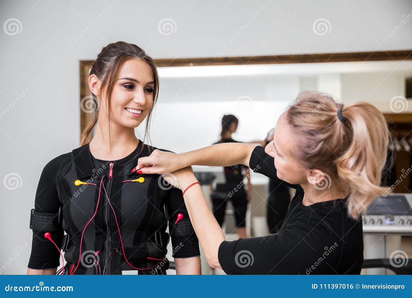 Instructor personal que pone los diodos del ccsme en mujer feliz joven