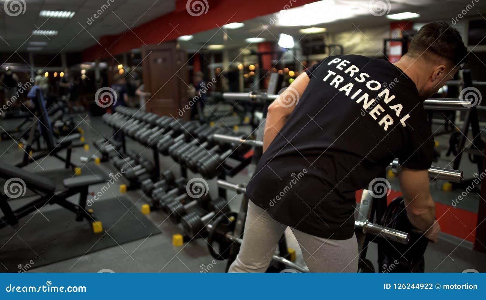 Instructor personal que prepara el sitio para su gimnasio de los clientes, profesión del entrenamiento del deporte