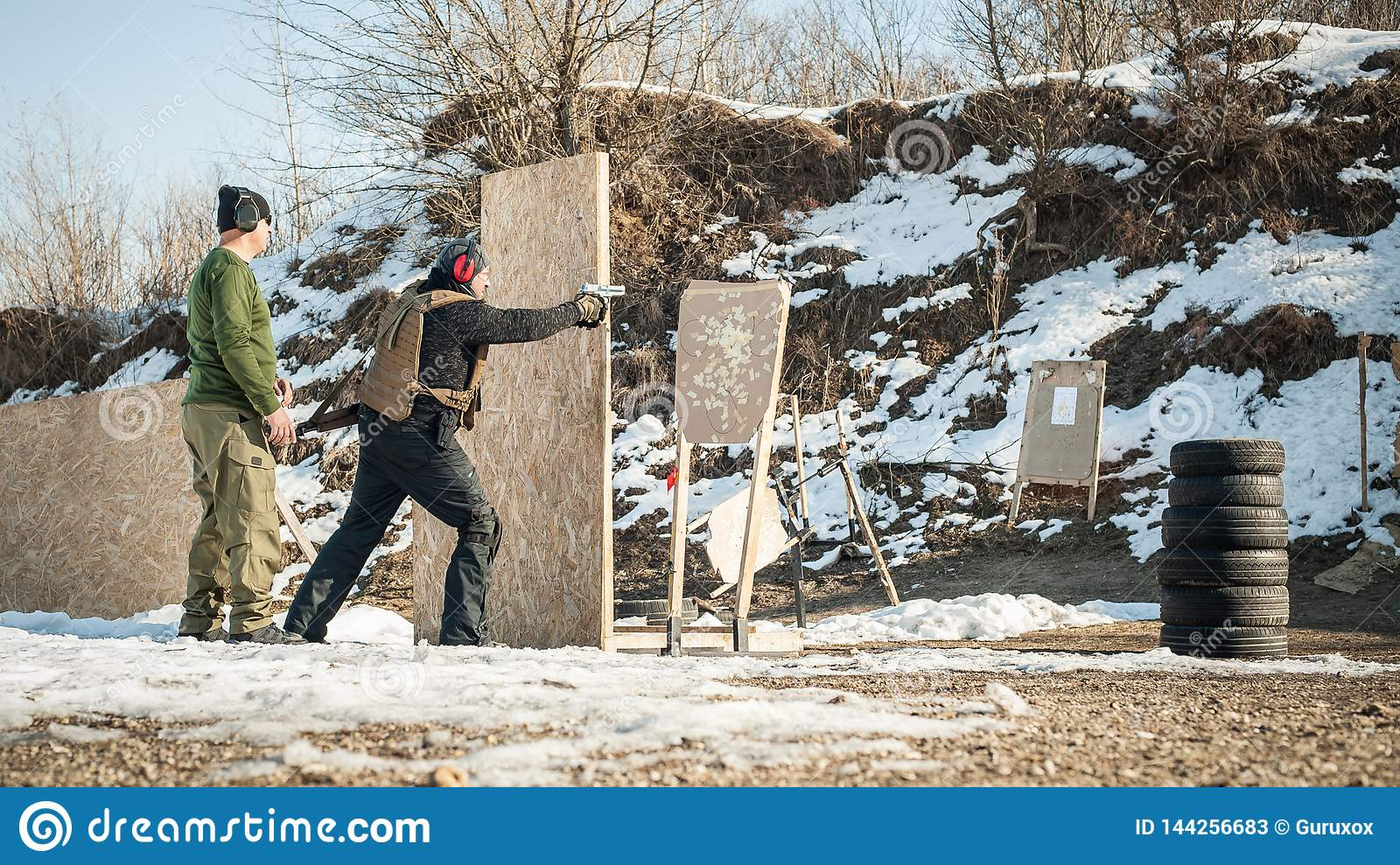 Instructor teaches student tactical gun shooting behind cover or barricade