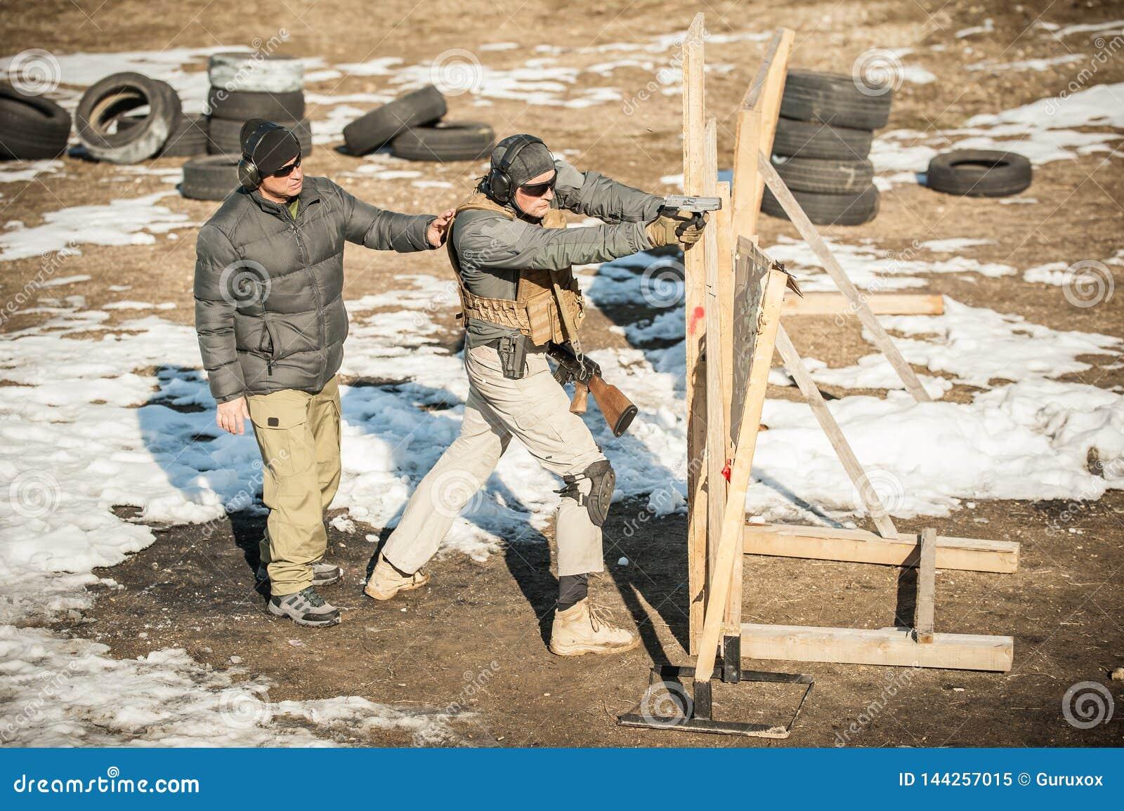 Instruktören undervisar studenten taktisk vapenskytte bak räkningen eller barrikaden