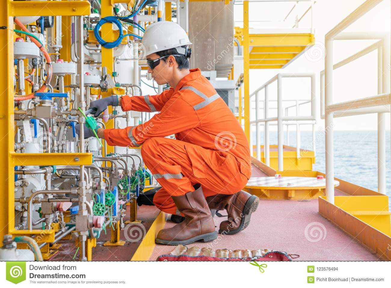 Instrument maintenance technician fixing chemical diaphragm pump at offshore oil and gas wellhead remote platform.