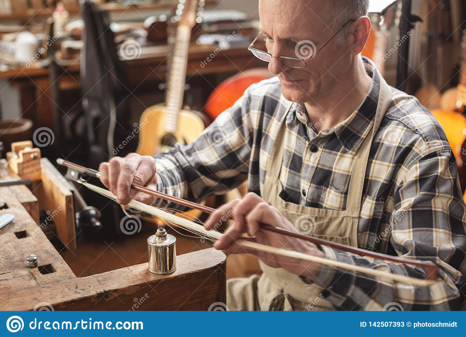 Mature instrument maker inside a rustic workshop is skillfully heating the hair of a violin bow to adjust its length. Blurred back
