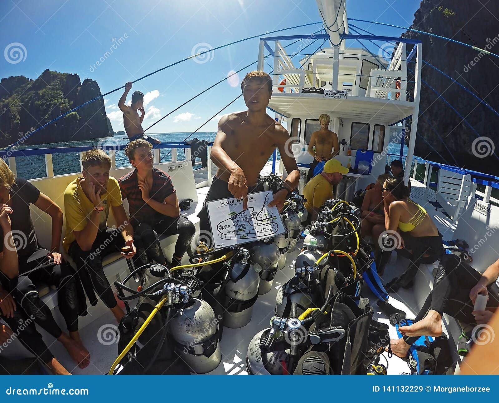 Instrutor asiático do mergulho que dá uma instrução do mergulho a um grupo de turistas