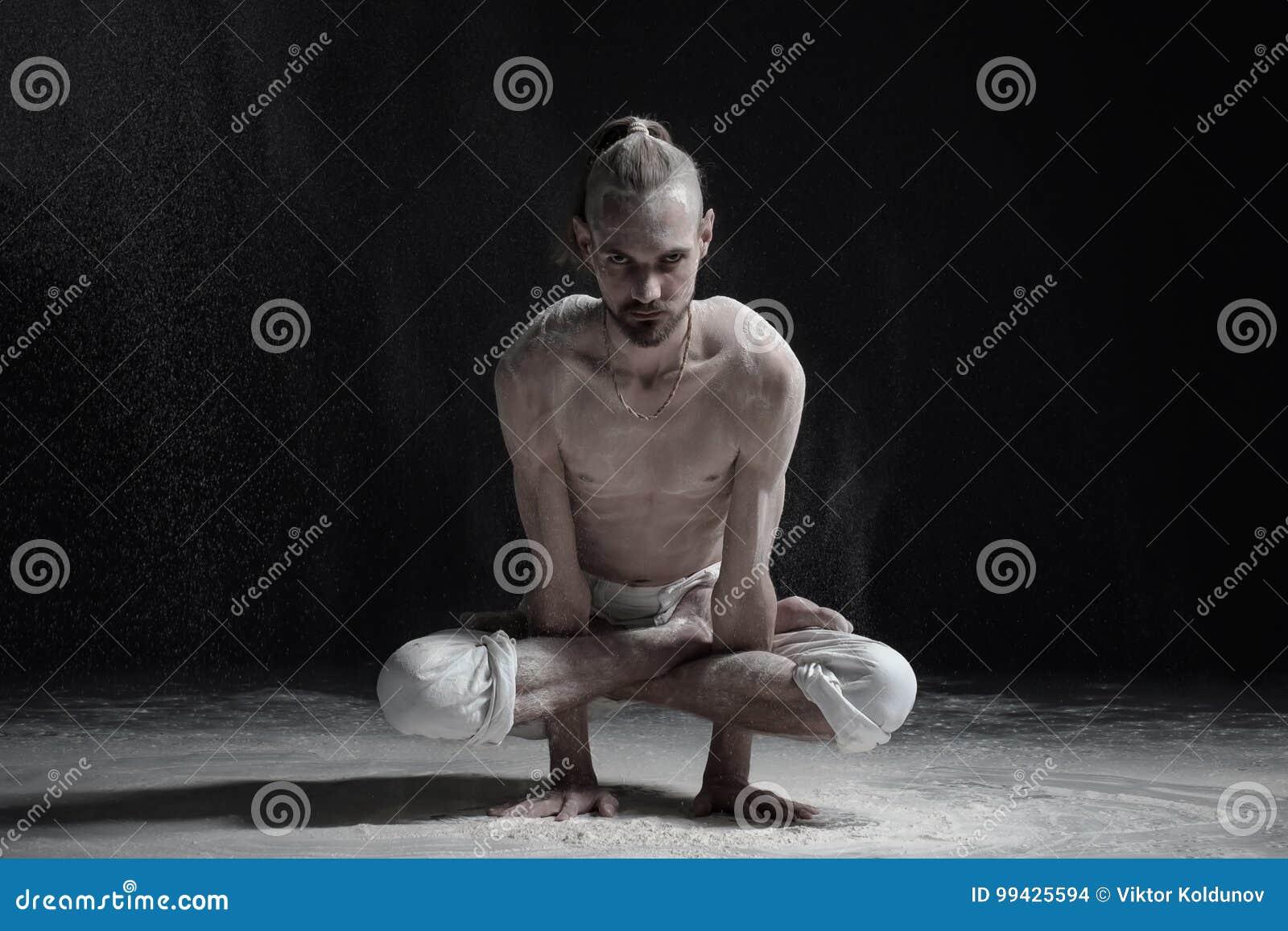 Instrutor caucasiano novo da ioga do homem que faz a postura Kukkutasana do galo da pose do galo