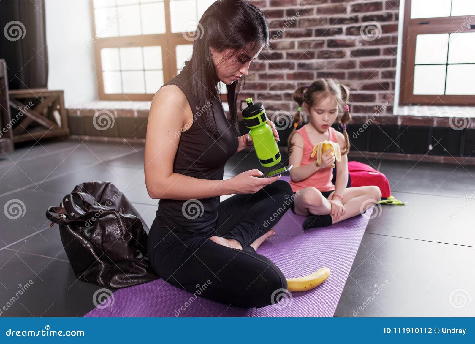Instrutor da criança da ioga e uma menina que tem uma ruptura após o exercício que senta-se na esteira que come o petisco, água p