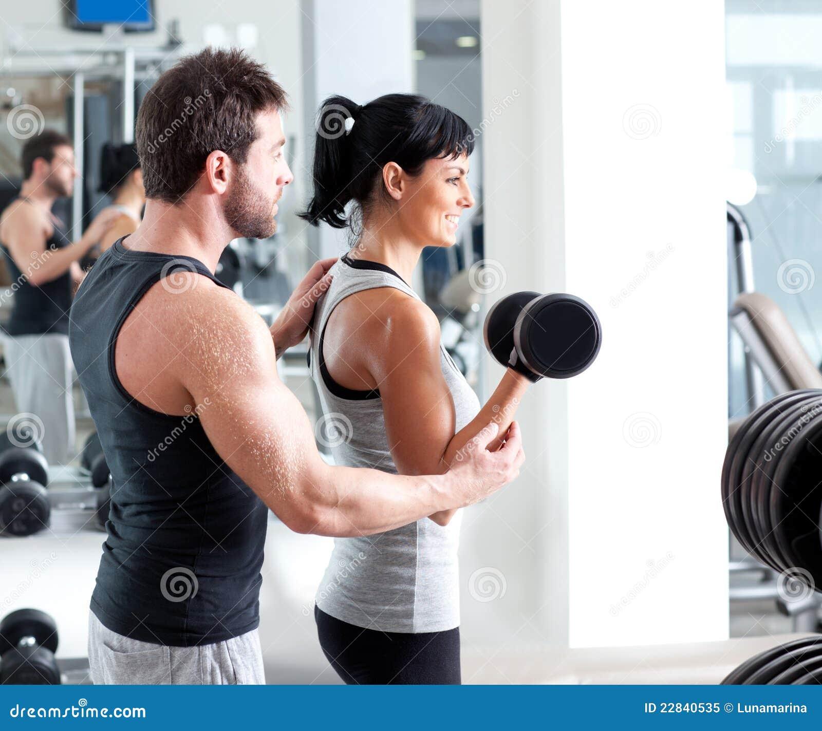 Instrutor pessoal da mulher da ginástica com treinamento do peso