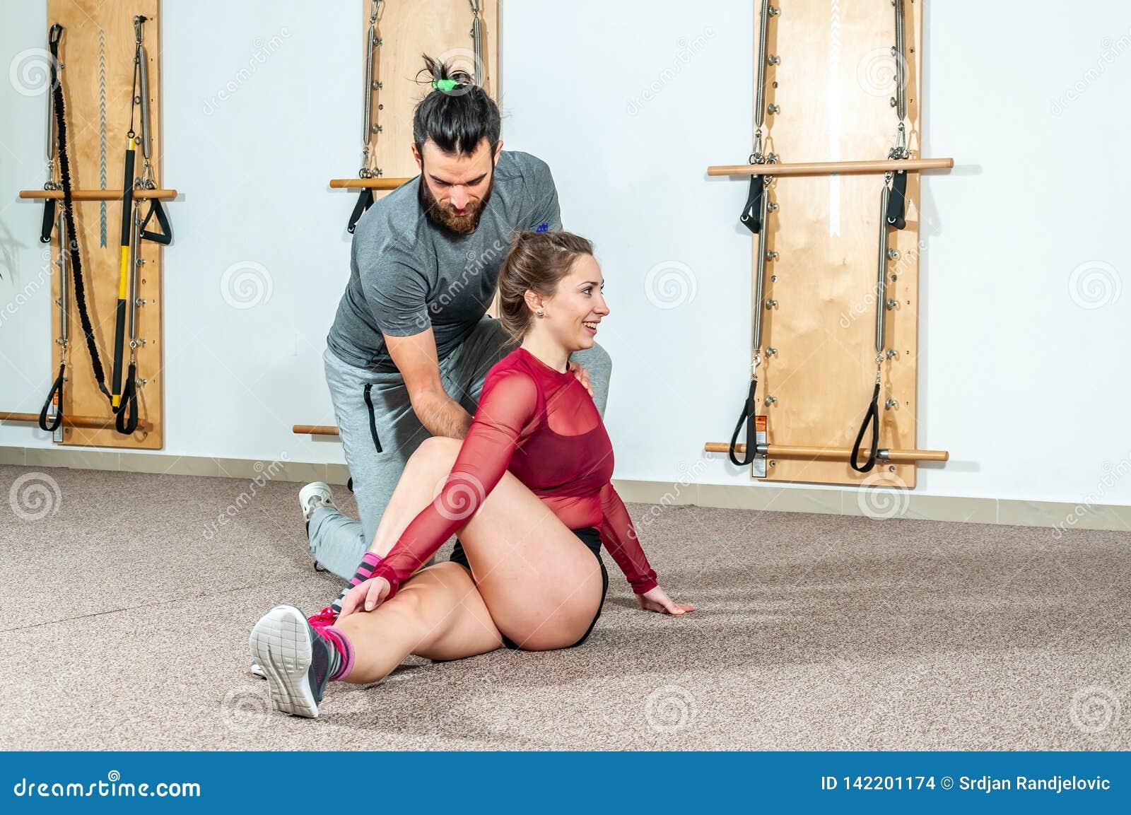 Instrutor pessoal masculino da ioga considerável com uma barba que ajuda a menina nova da aptidão a esticar seus músculos após o