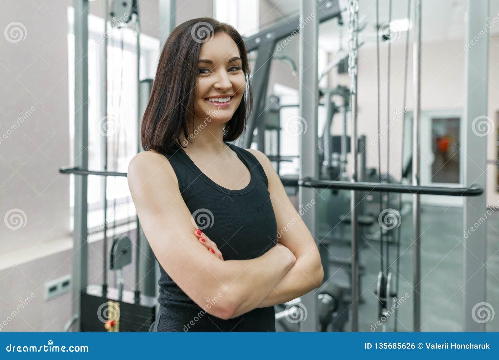 Instrutor seguro atlético novo da aptidão da mulher que levanta no gym com os braços cruzados dobrados, olhando in camera