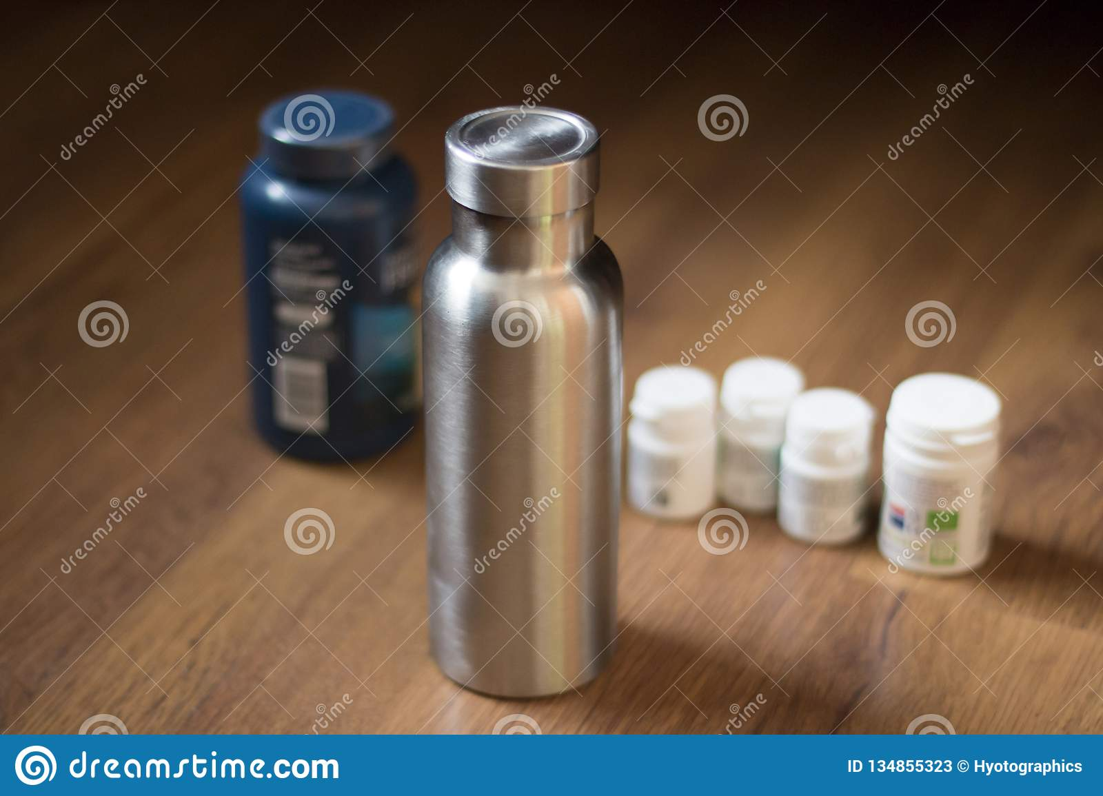 Insulated Stainless Bottle next to pill bottles