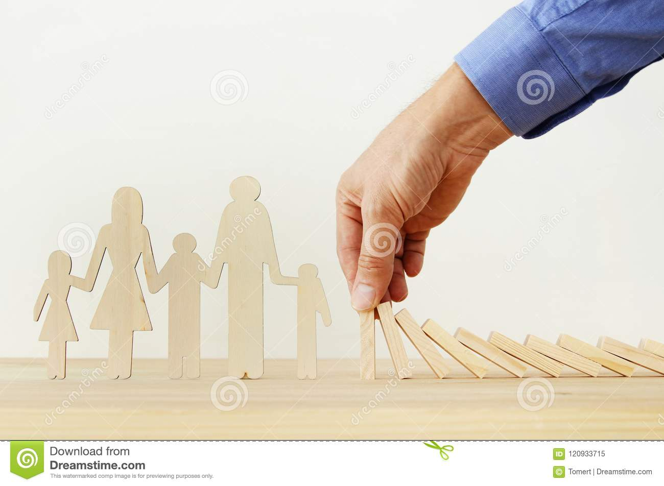 Insurance concept. Businessman protecting a family from domino effect. life, financial and health issues