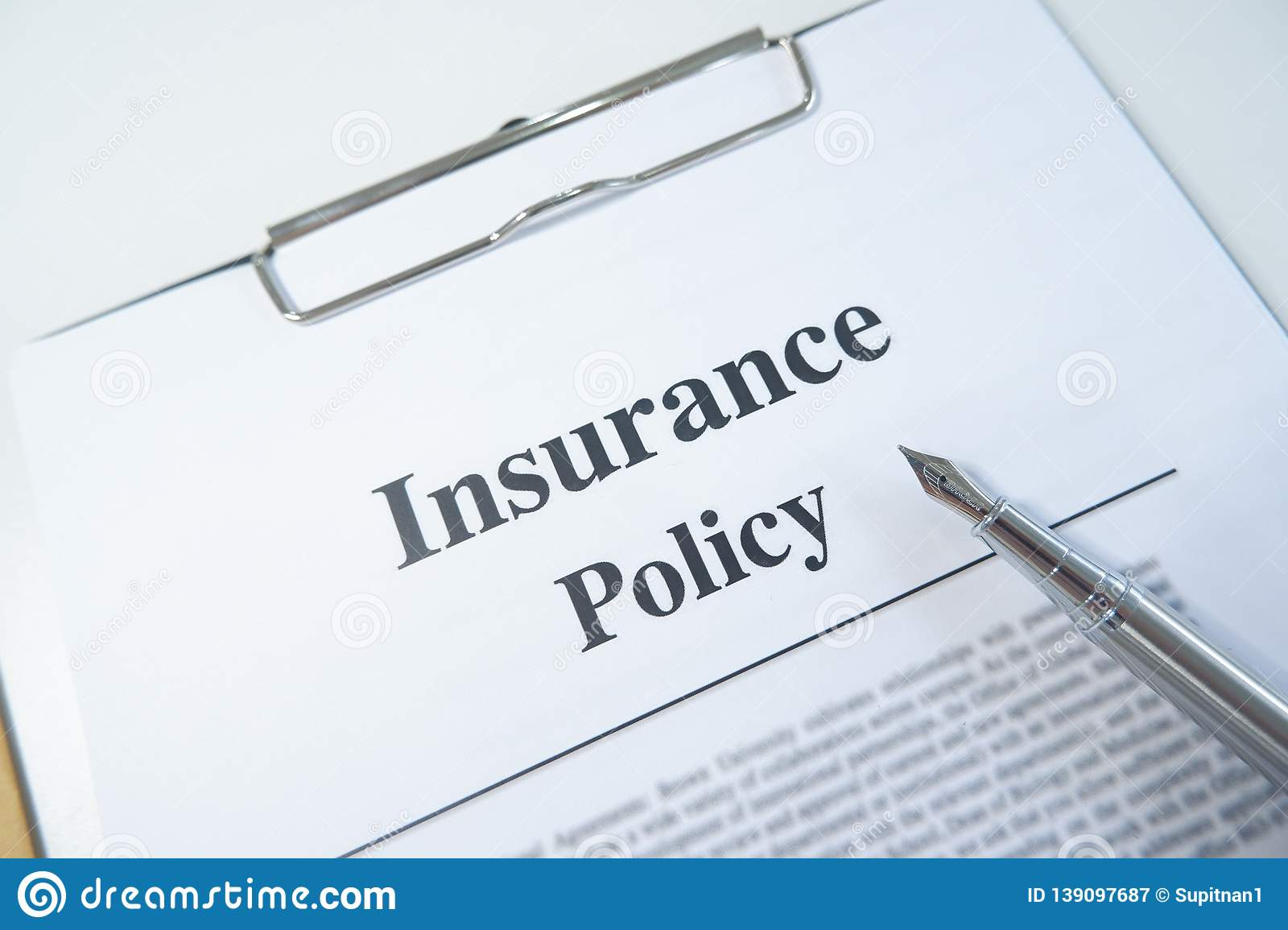 Insurance policy form and pen on desk in office showing risk concept. Life; Health, car, travel