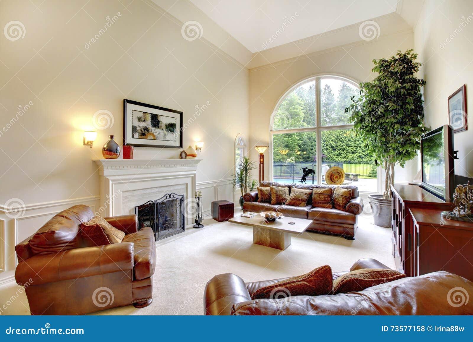 int rieur haut plafond de luxe de salon avec la chemin e les sofas en cuir et la fen tre. Black Bedroom Furniture Sets. Home Design Ideas