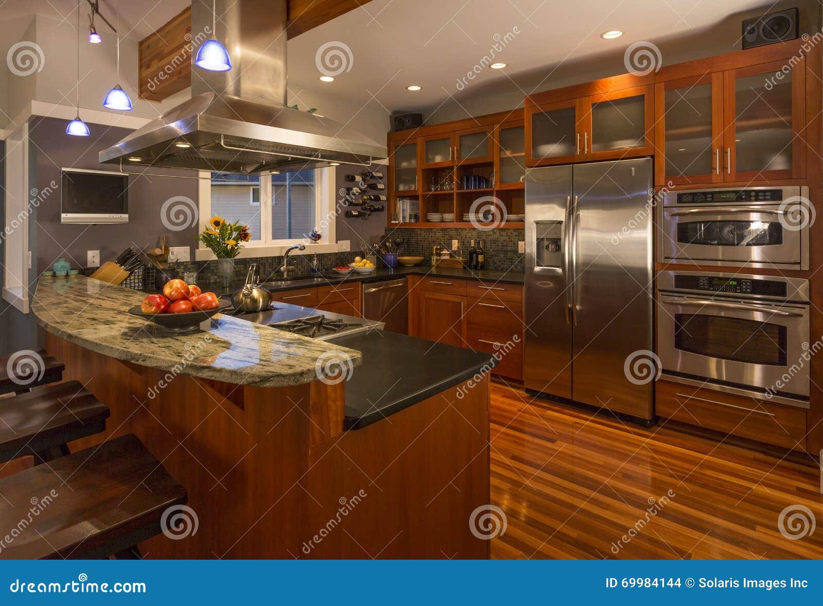 Intérieur à la maison classieux contemporain de cuisine avec les coffrets et les planchers en bois, la partie supérieure du compt