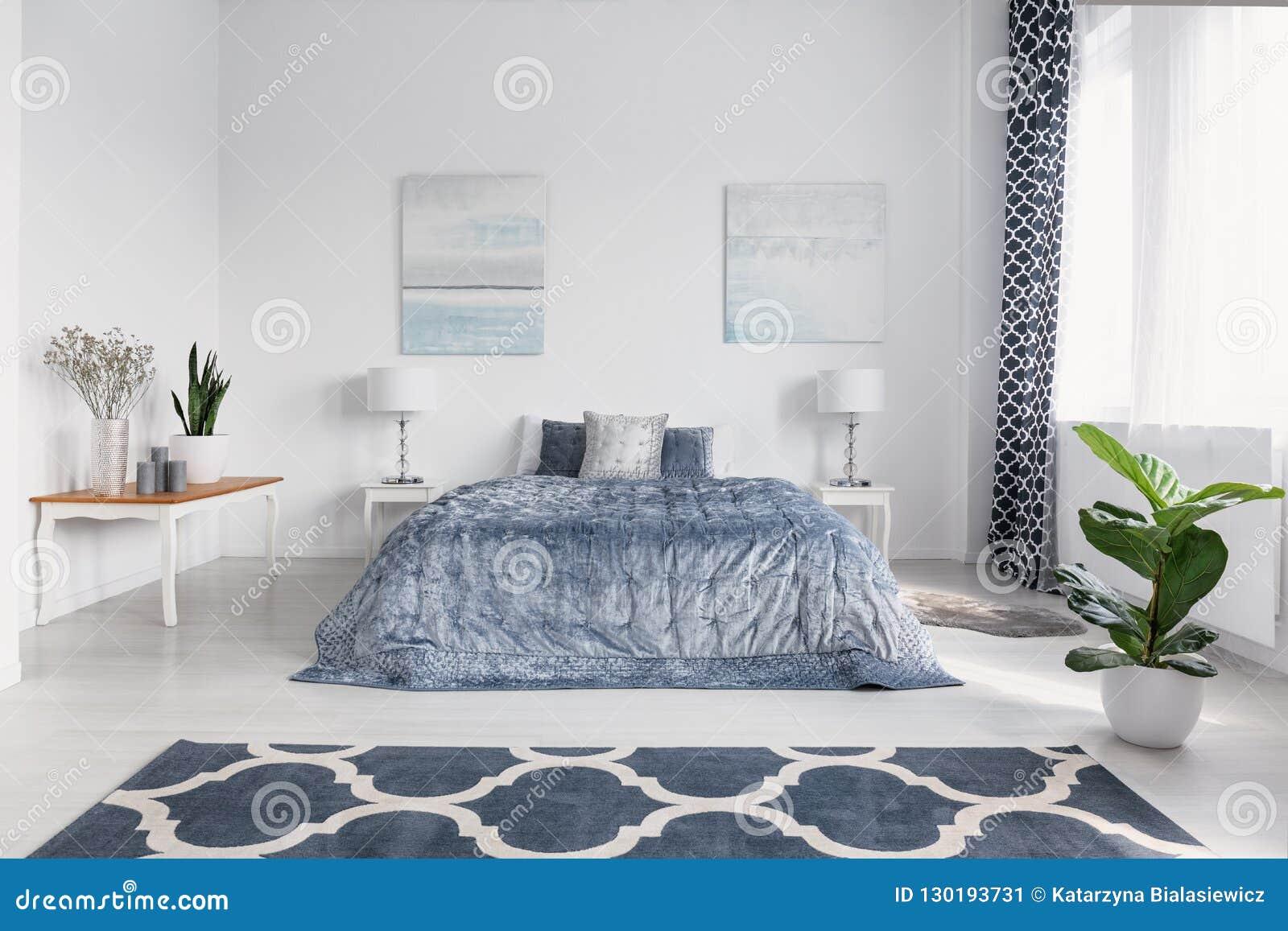Intérieur élégant de chambre à coucher avec le grand lit confortable avec la literie bleue, peintures sur le mur et tapis modelé
