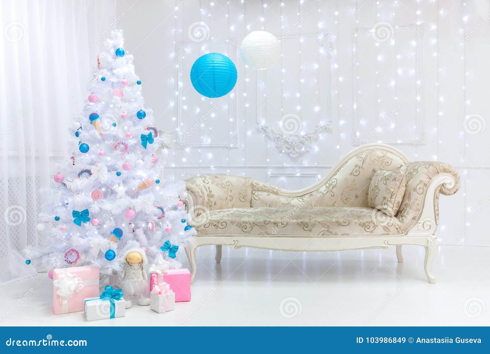 Intérieur classique de lumière de Noël dans les tons blancs, roses et bleus avec un divan, un arbre et un bâti