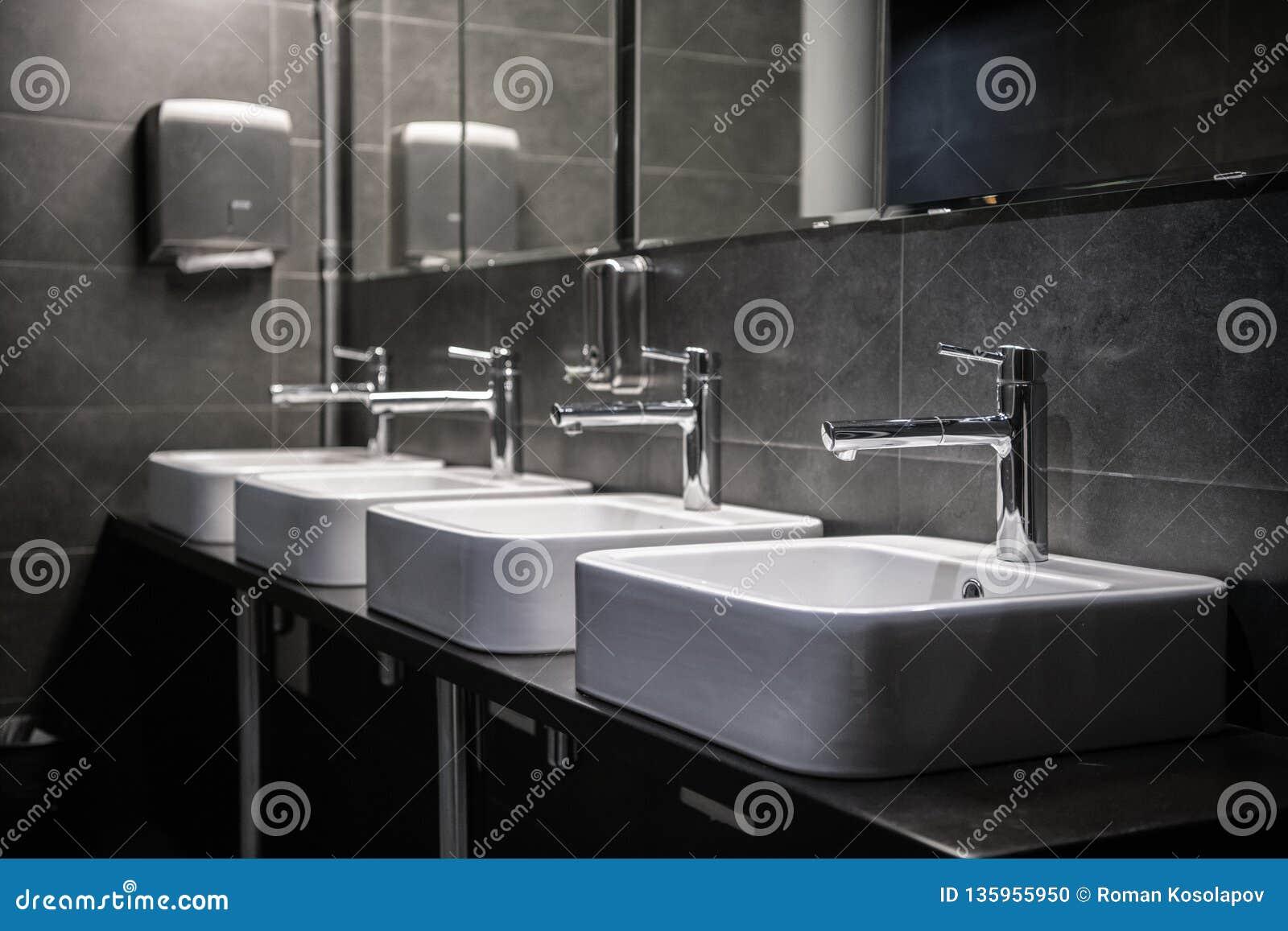 Intérieur d une toilette publique moderne de salle de bains dans des couleurs grises