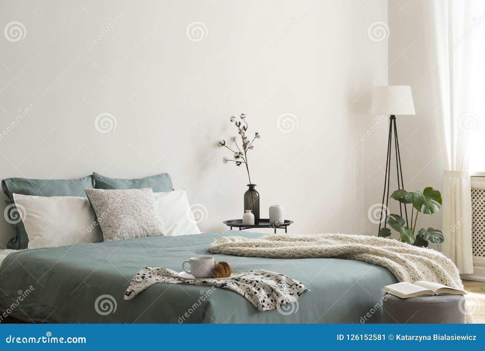 Intérieur de chambre à coucher avec des feuilles de vert sauge et de blanc et des coussins et une couverture Table noire en métal