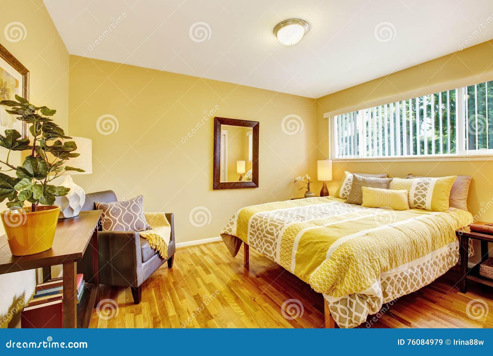 Intérieur de chambre à coucher dans des tons jaunes avec le plancher en bois dur