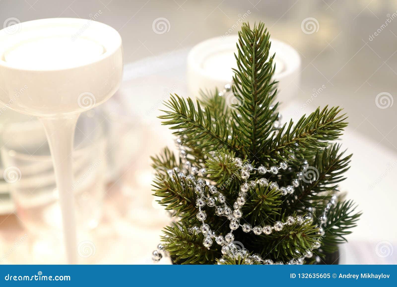Intérieur du ` s de nouvelle année Un petit arbre de Noël artificiel avec des jouets et des bougies Portion en verre