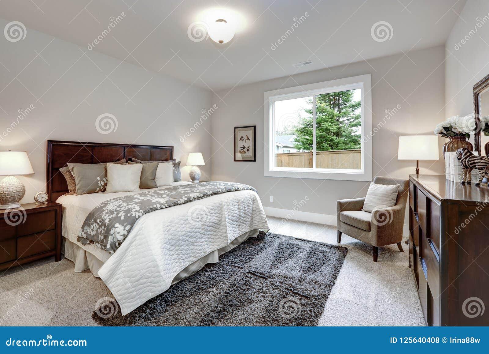 Intérieur moderne léger de chambre à coucher principale avec le lit et la raboteuse de darkwood