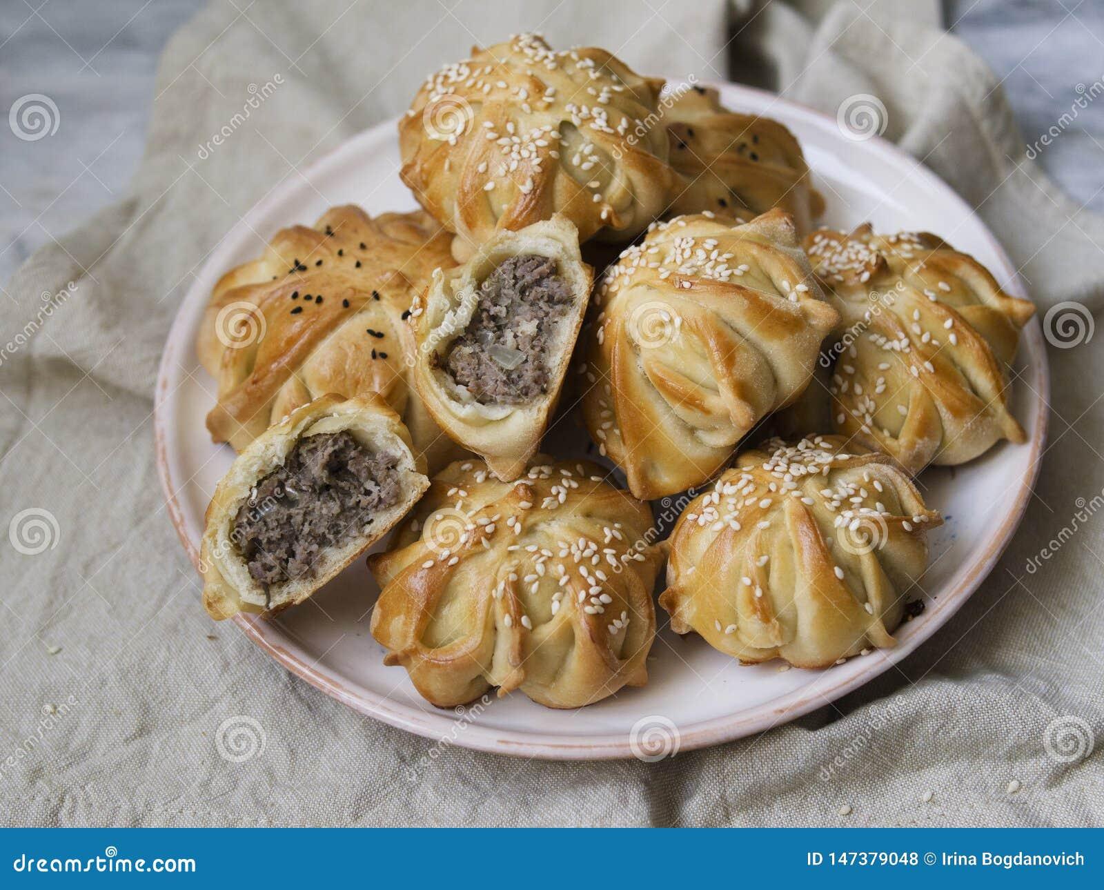 A int?ressant form? le mini tarte de viande fra?che Tartes d?licieux de samosa avec de la viande du plat sur le fond gris Morceau